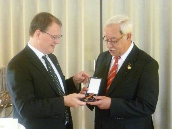 Uwe Dicken erhält aus der Hand des Landrates Olaf Schade das Bundesverdienstkreuz